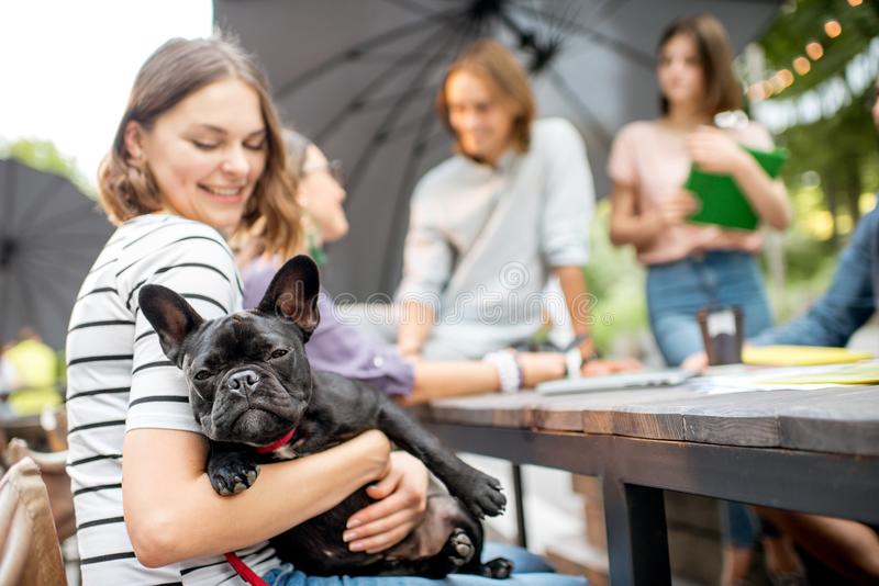 Friends having fun together with dog outdoors. Young friends having fun together sitting with french bulldog during a studying outdoors in the park royalty free stock image