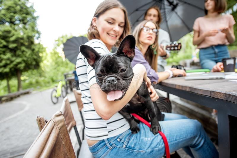 Friends having fun together with dog outdoors. Young friends having fun together sitting with french bulldog during a studying outdoors in the park royalty free stock photography