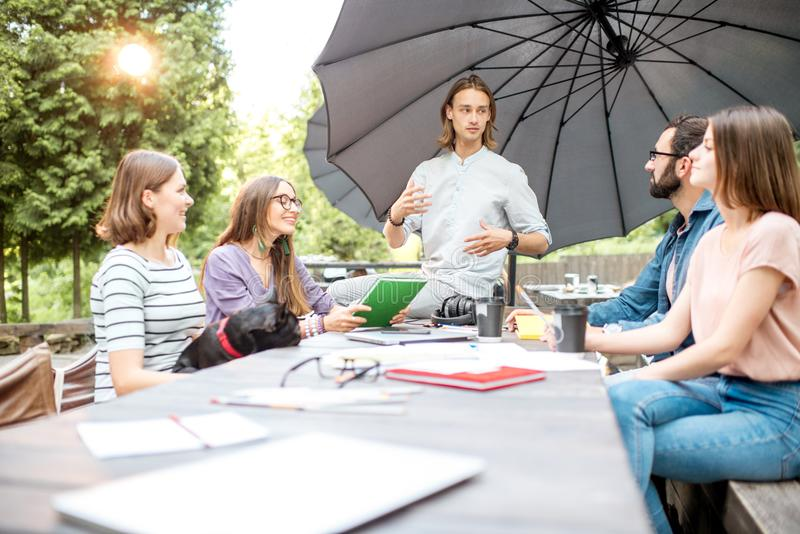 Friends having fun together during a study outdoors. Young friends having fun talking together during a studying outdoors in the park royalty free stock photo