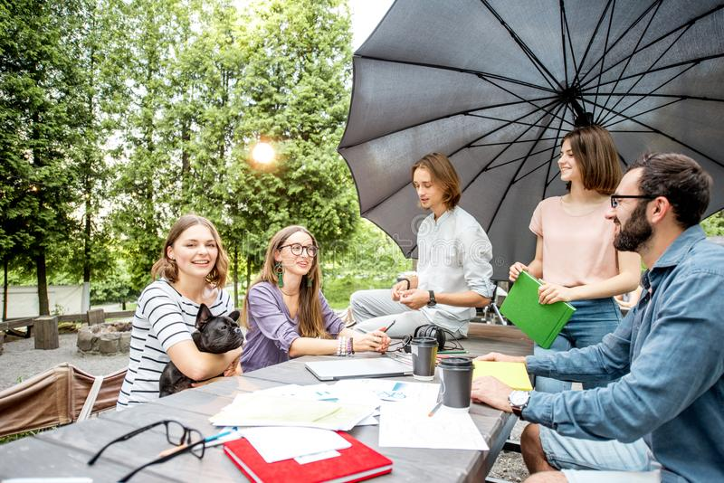 Friends having fun together during a study outdoors. Young friends having fun talking together during a studying outdoors in the park royalty free stock image