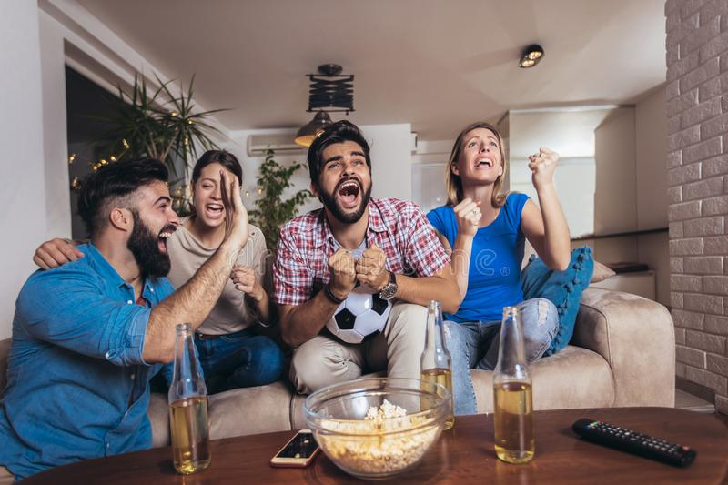 Friends having fun by watching football match at home stock photos
