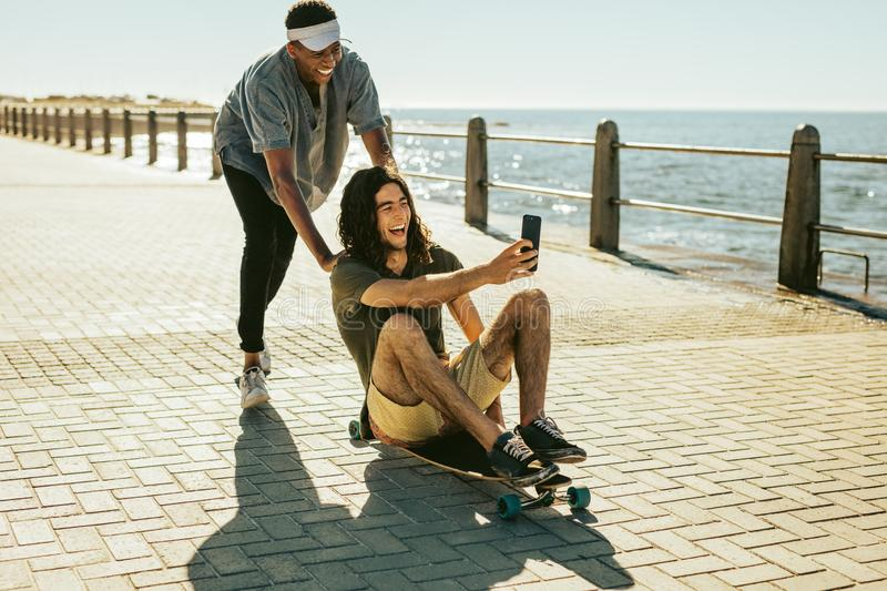 Friends having a great time together. Cheerful friends playing on the skateboard outdoor and taking a selfie. Young guy taking selfie while sitting on skateboard stock photography