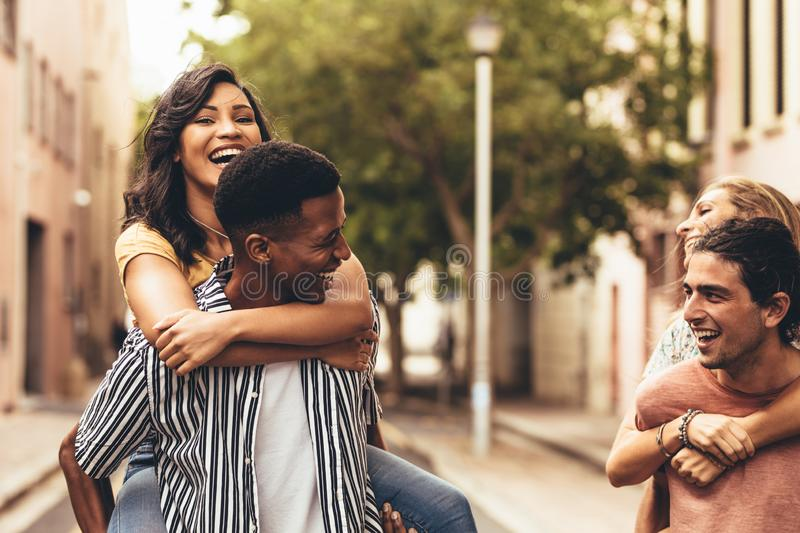 Friends having great time together. Two young men carrying a females friends their back and smiling. Group of friends piggybacking outdoors on city street royalty free stock photography