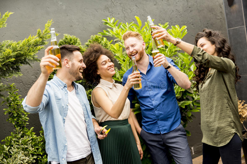 Friends having outdoor garden party toast with alcoholic cider d. Group of friends having outdoor garden party toast with alcoholic cider drinks stock photos