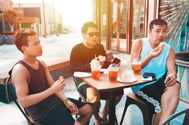 Friends having a snack. A group of male friends having a snack in an outdoor cafe stock images