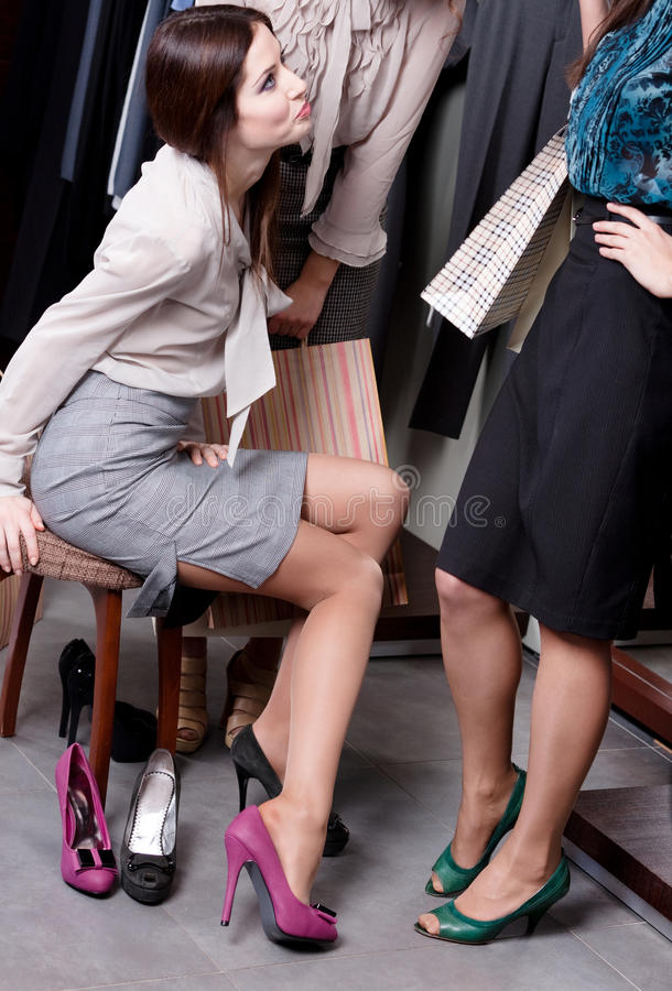 Friends help to select an appropriate shoes. Friends help to select an appropriate fuchsia shoes stock image