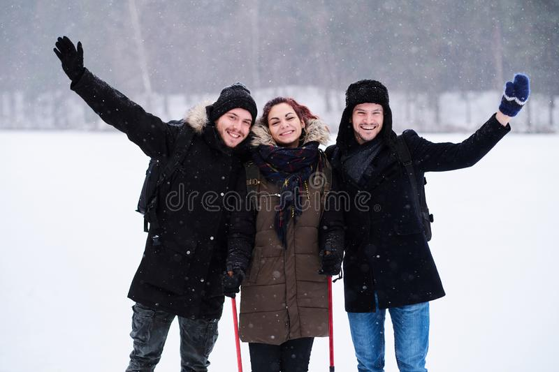 Friends walk in the cold snowy forest stand in a hug and look at the camera. Friends hiking in the cold snowy forest stand in a hug and look at the camera stock images