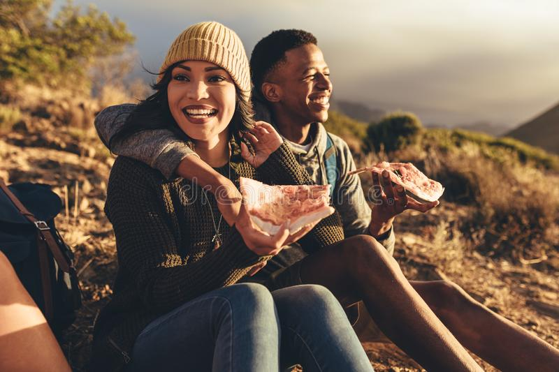 Friends on hiking trip having pizza. Two friends having pizza sitting on mountain trail. Man and women on hiking trip eating pizza royalty free stock images