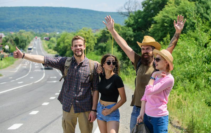 Friends hitchhikers looking for transportation sunny day. Family weekend. Company friends travelers hitchhiking at edge. Road nature background. Company friends royalty free stock photo