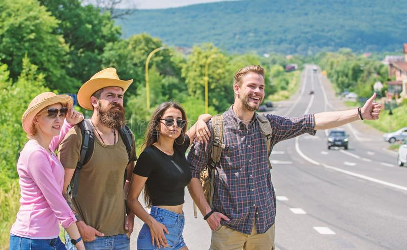 Friends hitchhikers looking for transportation sunny day. Family weekend. Company friends travelers hitchhiking at edge. Road nature background. Begin great stock photography