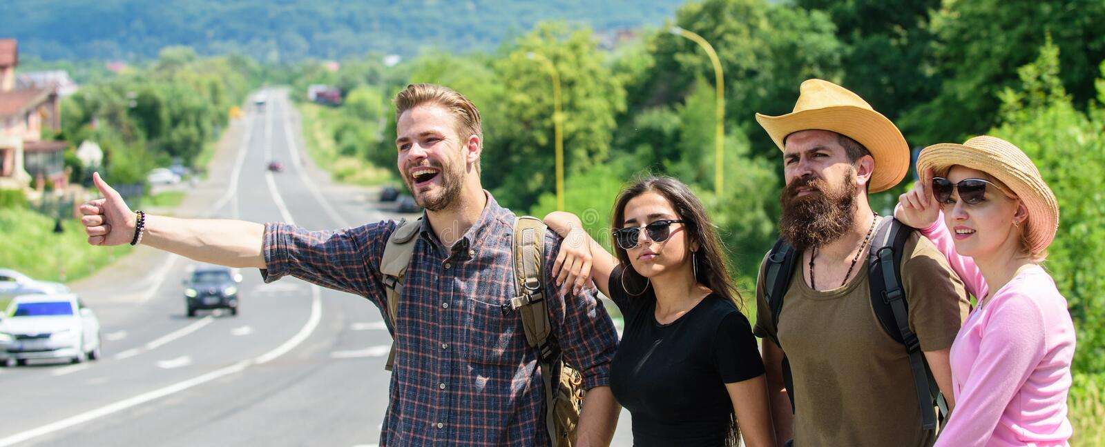 Friends hitchhikers looking for transportation sunny day. On way to vacation. Company friends travelers hitchhiking at. Edge road nature background. Begin great stock images