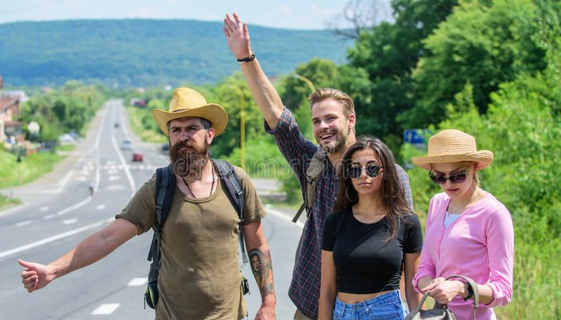 Friends hitchhikers travelling summer sunny day. Begin great adventure in your life with hitchhiking. Travellers try to stock photo