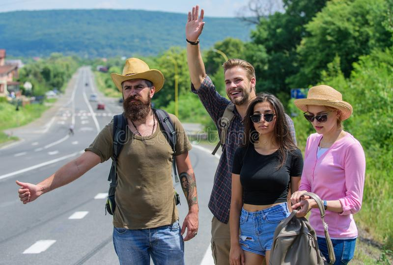 Friends hitchhikers travelling summer sunny day. Travellers try to stop car. Company friends travelers hitchhiking at. Edge road nature background. Begin great royalty free stock images