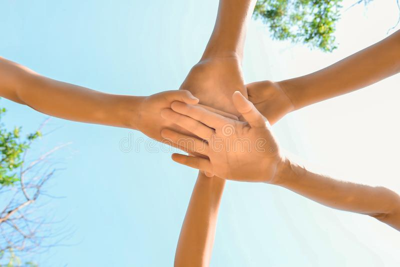 Friends hold hands together, bottom view of a group of people clasped hands stock photography