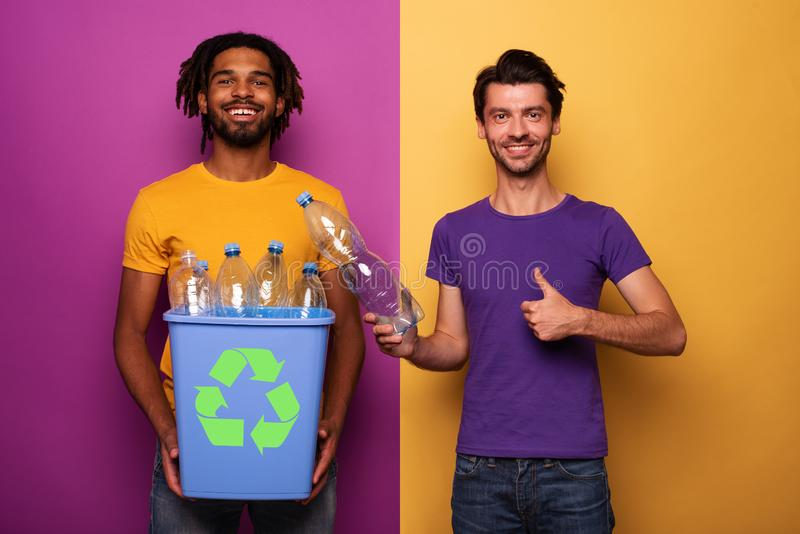 Friends hold a plastic container with bottles over yellow and purple color. Concept of ecology, conservation, recycling royalty free stock photography