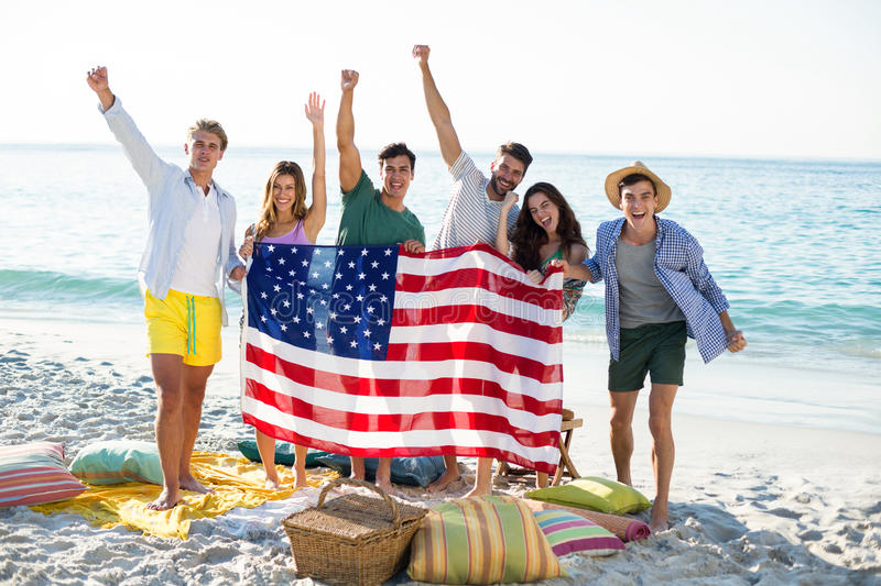 Friends holding American flag while standing on shore. Happy friends holding American flag while standing on shore at beach stock photos