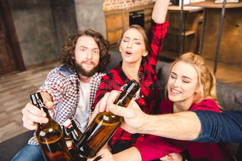 Friends holding beer bottles. Smiling friends holding beer bottles while sitting on sofa stock photo