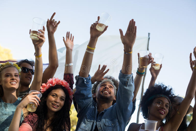 Friends holding beer glasses while enjoying music festival. Low angle view of friends holding beer glasses with arms raised while enjoying music festival stock photography