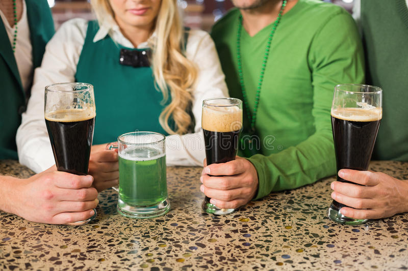 Friends holding beers. Men holding normal beers while women holds green beer stock photo