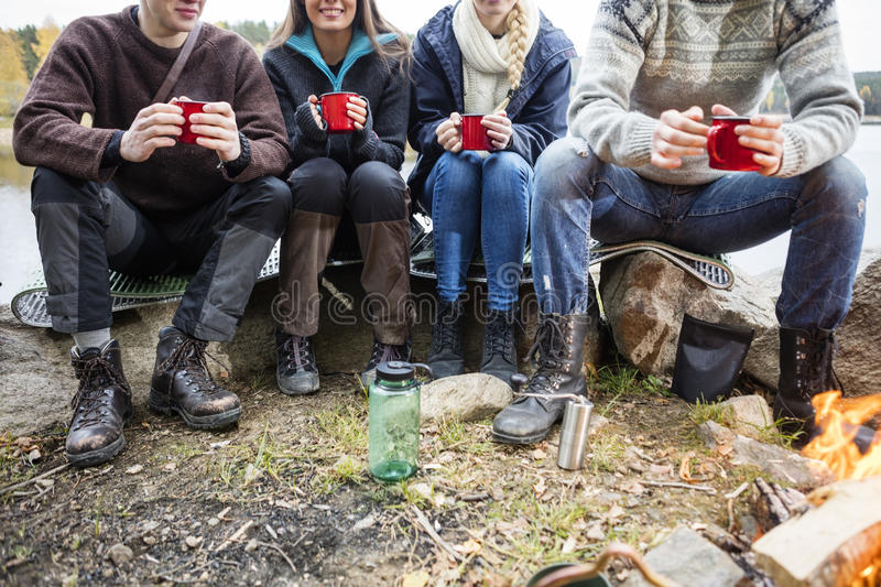Friends Holding Coffee Cups At Campsite royalty free stock photos