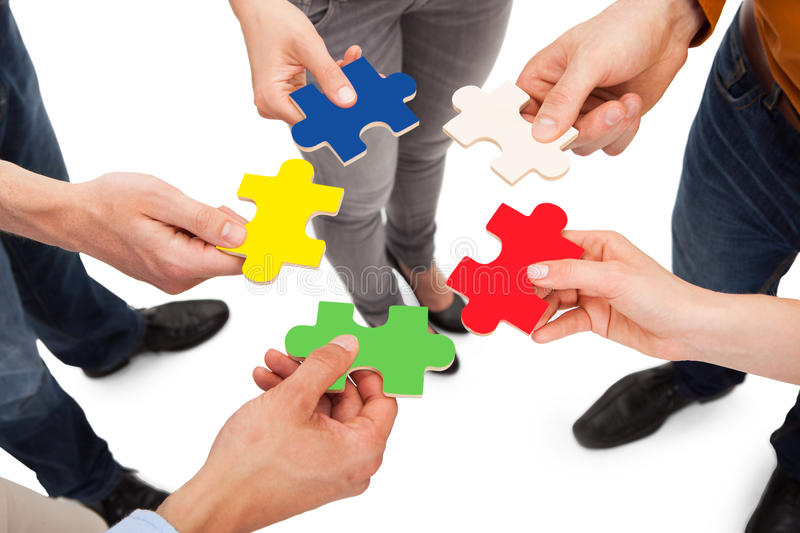 Friends holding colorful jigsaw pieces. Closeup of young friends holding colorful jigsaw pieces over white background stock photo