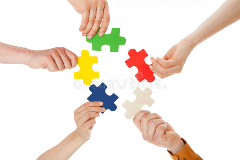 Friends holding colorful jigsaw pieces. Closeup of young friends holding colorful jigsaw pieces over white background royalty free stock photos