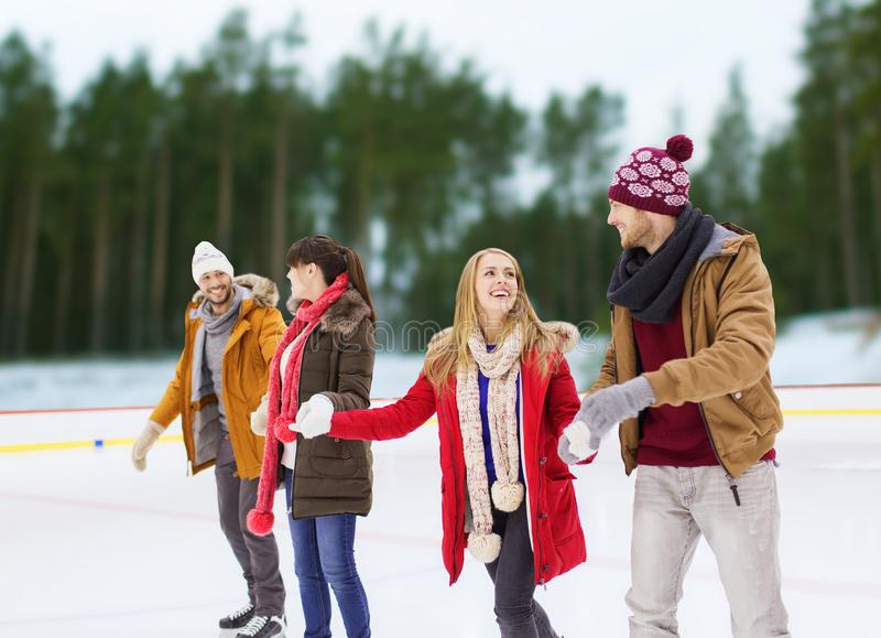 Friends holding hands on outdoor skating rink. Friendship, winter and leisure concept - happy friends holding hands on skating rink over outdoor background stock images