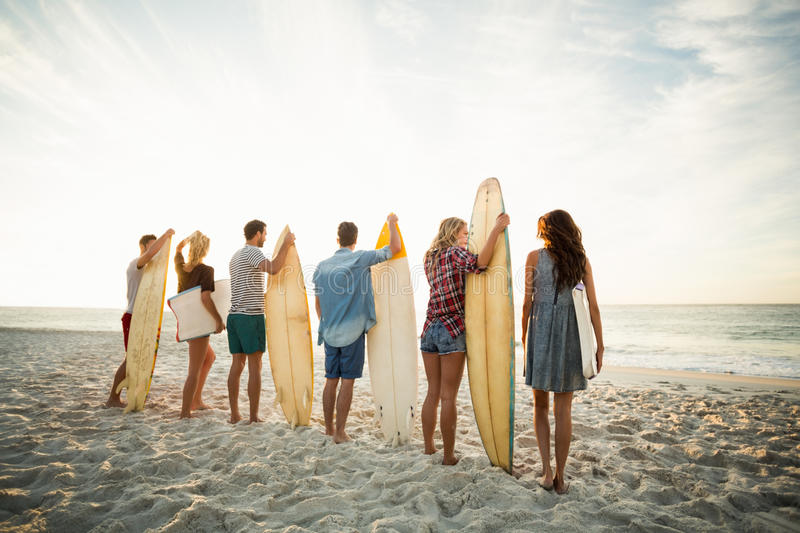 Friends holding surfboard on the beach stock photos