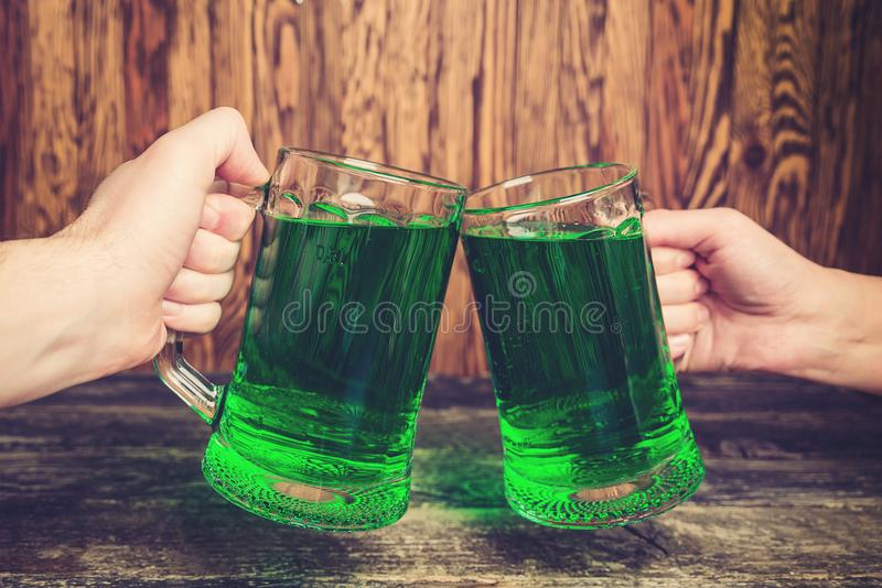 Friends, holding two mug of green beer against wooden wall. stock photography