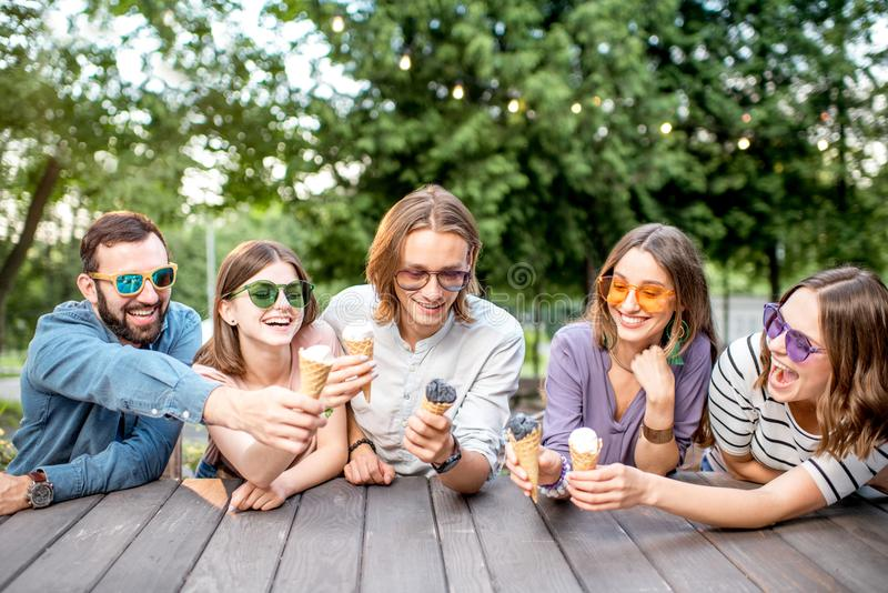 Friends with ice cream in the cafe. Young friends having fun with ice cream sitting together outdoors in the park stock photos