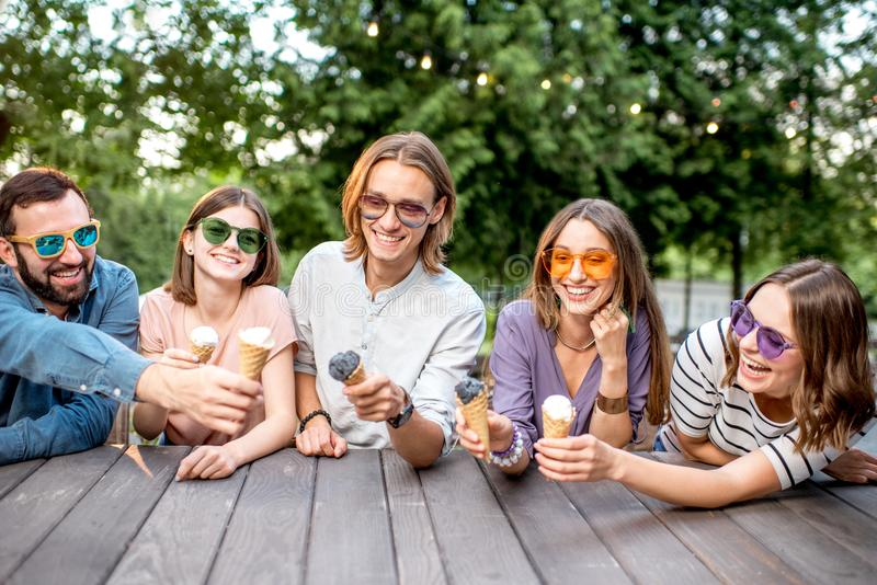 Friends with ice cream in the cafe. Young friends having fun with ice cream sitting together outdoors in the park stock images