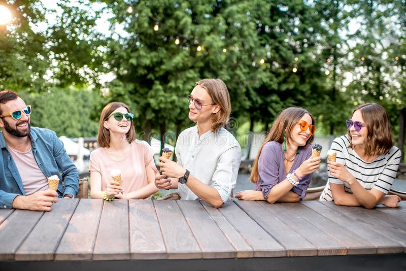 Friends with ice cream in the cafe. Young friends having fun with ice cream sitting together outdoors in the park royalty free stock image