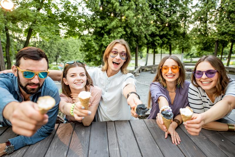 Friends with ice cream in the cafe. Young friends having fun with ice cream sitting together outdoors in the park stock photo
