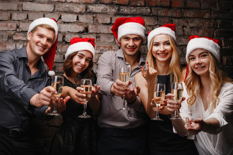 Friends invite to join to Christmas celebration. New Year, event, party, holiday, fun. Company of cheerful friends in Santa caps invite to join to Christmas royalty free stock photography