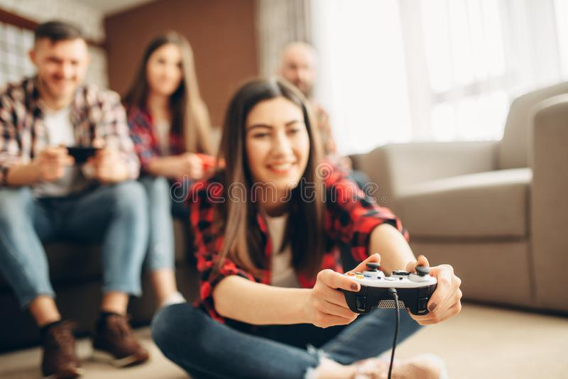 Friends with joysticks plays tv console at home. Smiling friends with joysticks plays tv console at home. Group of gamers with joypads playing videogame, male royalty free stock images
