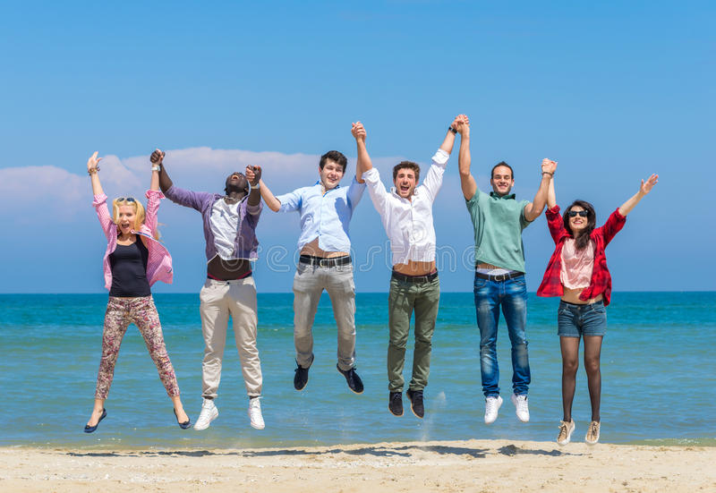 Friends jumping on the beach stock images