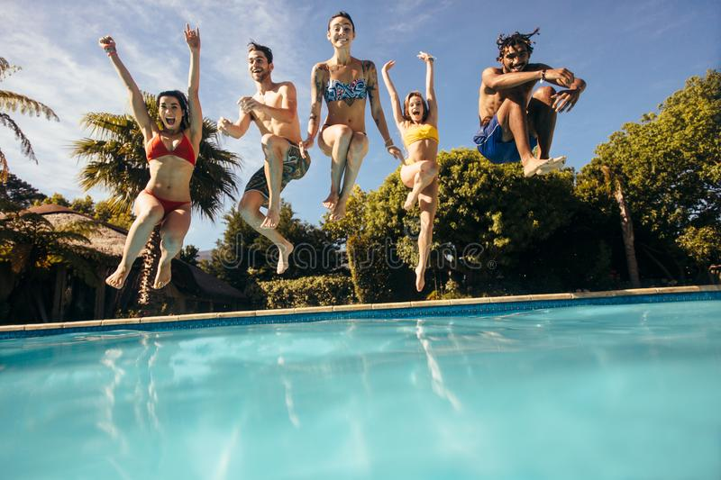 Friends jumping into a swimming pool and having fun. Happy young friends jumping into outdoor swimming pool and having fun. Group of men and women jumping into a royalty free stock photography