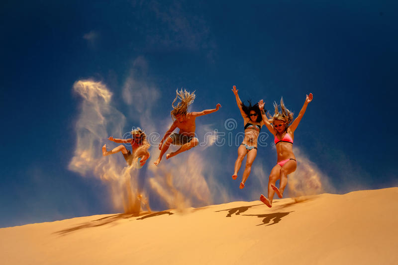 Friends jumping on the yellow sand dune. royalty free stock image