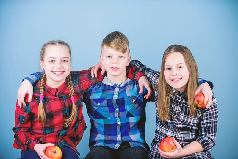 Friends kids hug each other. Healthy lifestyle. Boy and girls friends in similar checkered clothes eat apple. Teens with stock photos