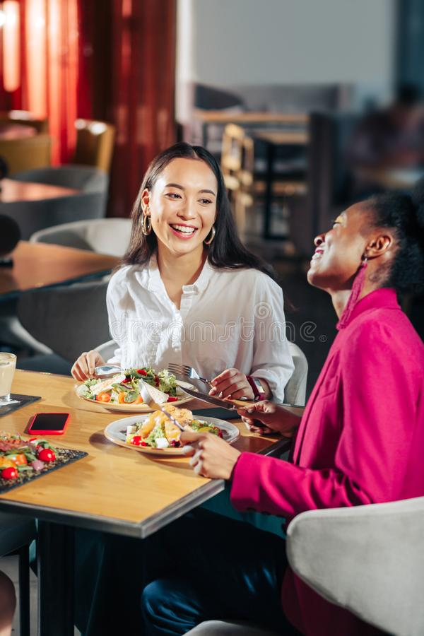Friends laughing while communicating in a big restaurant. Friends laughing. Best cheerful friends laughing while communicating in restaurant stock image