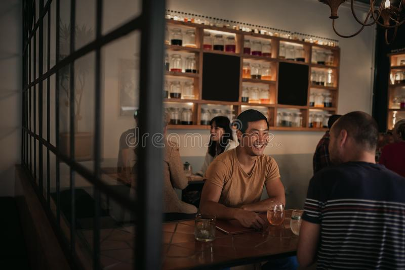 Friends laughing over drinking in a bar together at night stock photos