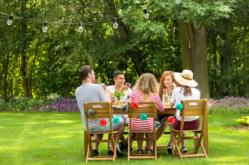 Friends laughing, sitting at a garden table, eating a vegetarian. Meal and telling jokes royalty free stock images