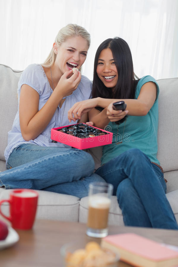 Friends laughing at tv and sharing box of chocolates stock image