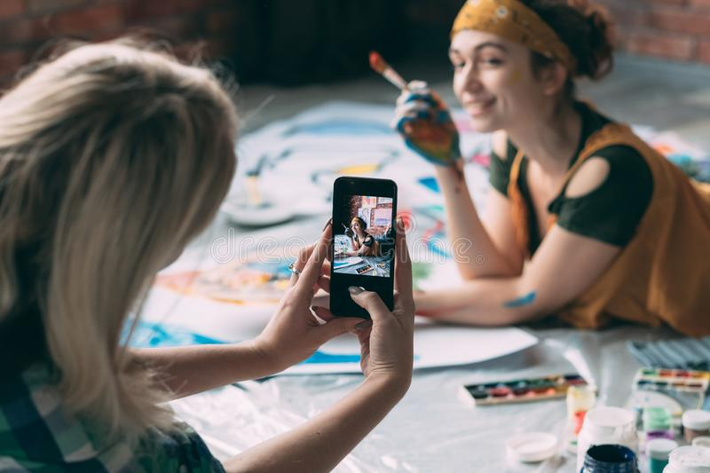 Friends leisure picture artist floor paint smiling. Friends leisure. Lady taking picture of young female artist posing on floor with paint and brush, smiling stock image