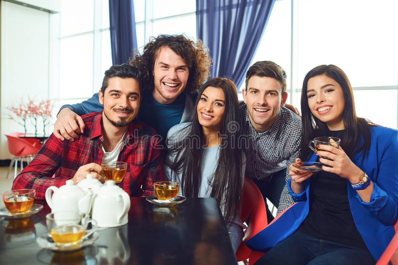Friends are looking at the camera sitting at a table in a cafe. Cheerful friends are looking at the camera while sitting at a table in a cafe. Meeting friends royalty free stock photography