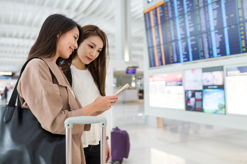 Friends looking for flight number in airport. Beautiful young asian woman stock photo