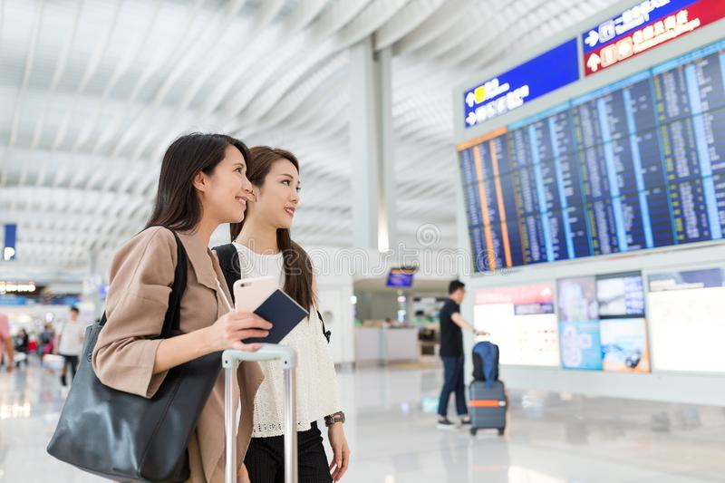 Friends looking for flight number in Hong Kong airport. Asian young woman stock photo