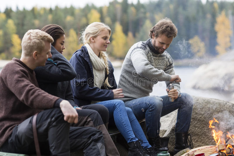 Friends Looking At Man Grinding Coffee At Campsite stock photo
