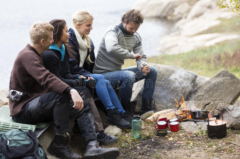 Friends Looking At Man Grinding Coffee At Campsite stock photography