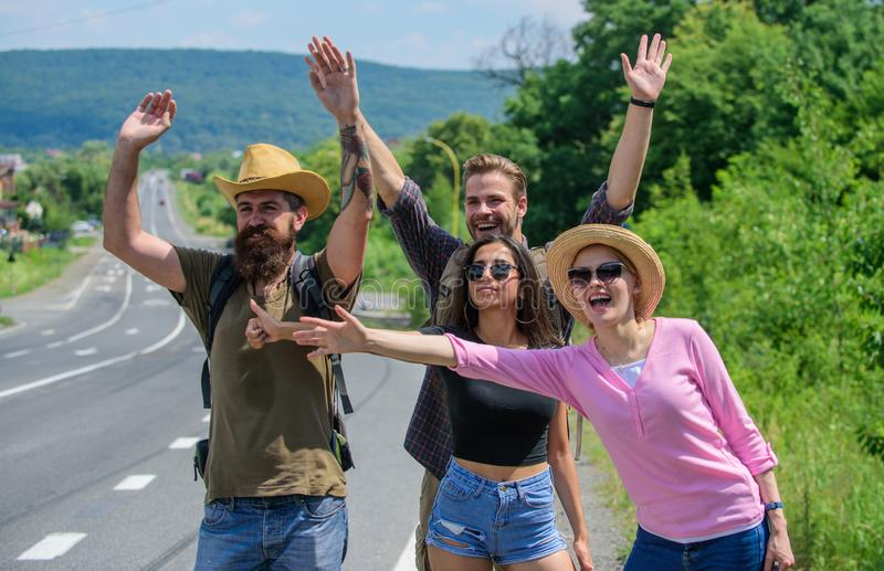 Friends looking for transportation. Friends hitchhikers travelling sunny day. Company friends travelers hitchhiking at. Edge road nature background. Begin great stock photo